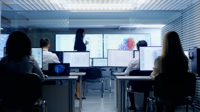 chief female computer engineer holds office briefing in the neural network machine learning research center. - apprendimento automatico video stock e b–roll
