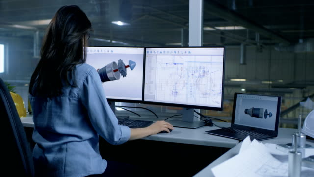 chief female engineer designs on 3d model of a turbine or engine part. second monitor shows technical blueprints. out of the office window big factory is seen. - inżynieria filmów i materiałów b-roll