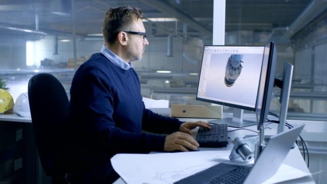 chefingenieur männlich arbeiten an großen technischen projekt erstellen 3d turbine / motor modell auf seinem persönlichen computer. er nutzt cad-software.out des großen fensterfabrik büro wird gesehen. - pflicht stock-videos und b-roll-filmmaterial