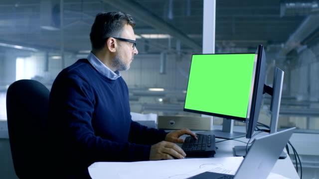 şef erkek teknik proje onun kişi bilgisayar üzerinde çalışan mühendis. i̇kinci ekran gösterir mock-up yeşil ekran. ofis pencere büyük fabrika dışında görülmektedir. - masaüstü bilgisayar stok videoları ve detay görüntü çekimi