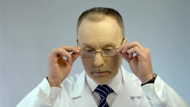 Chief physician putting on glasses, ready to examine patient, looking at camera Chief physician putting on glasses, ready to examine patient, looking at camera lab coat stock videos & royalty-free footage