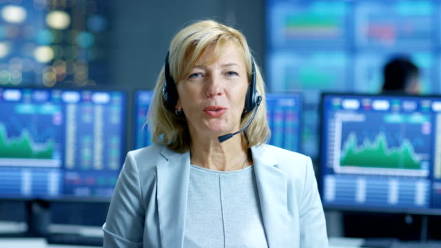 Chief Sales Force Representative Talks into the Headset. Behind Her People Working, Screens Show Stock Market Ticker Numbers and Graphs. video