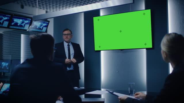 理事・ モニター ルームで緑モックアップ画面を使用してビジネス パートナーに最高戦略責任者を示すレポート。 - スパイ点の映像素材/bロール