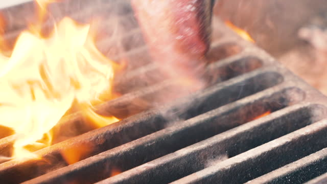 Chief using the spatula and turning the meat on the grill. Fire is burning, hot juicy oil steak cooking close up slow motion. Grill, tasty beefsteak slow motion close up