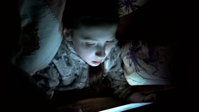 ett barn, en liten flicka, gömde sig under en filt på sängen på natten och spelar på en surfplatta i mörkret. koncept video. internet beroende. närbild av ansiktet. raw-video. 4k. - digital reading child bildbanksvideor och videomaterial från bakom kulisserna
