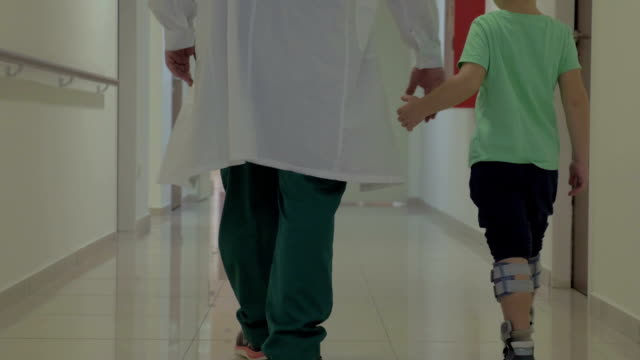 Child and doctor walking in hospital hallway video