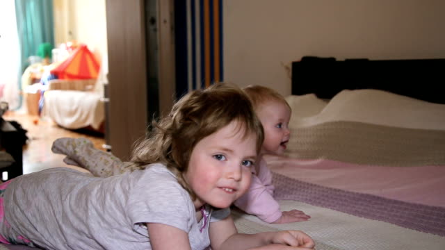 Child and her newborn sister on the bed video
