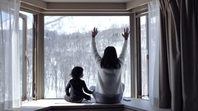 ett barn och hans mamma sitter nära ett fönster och tittar på snö som faller i skogen.. - snow kids bildbanksvideor och videomaterial från bakom kulisserna