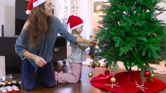 child and mother decorating christmas tree video