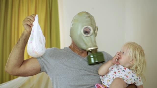 vídeos de stock e filmes b-roll de child and the man in a gas mask with disgust holding a diaper. - cheiro desagradável