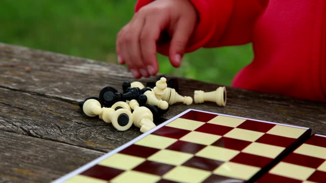 Child arranging chess pieces on the chessboard