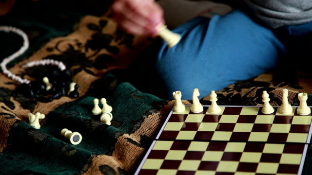 Child arranging white chess pieces on the board video