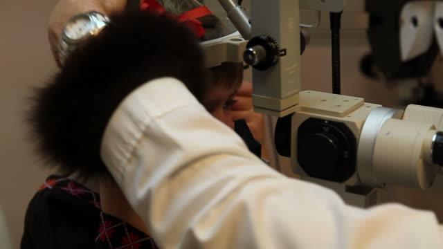 HD: Child at Optometrist Eye Check Up in Dark Room  eye exam stock videos & royalty-free footage