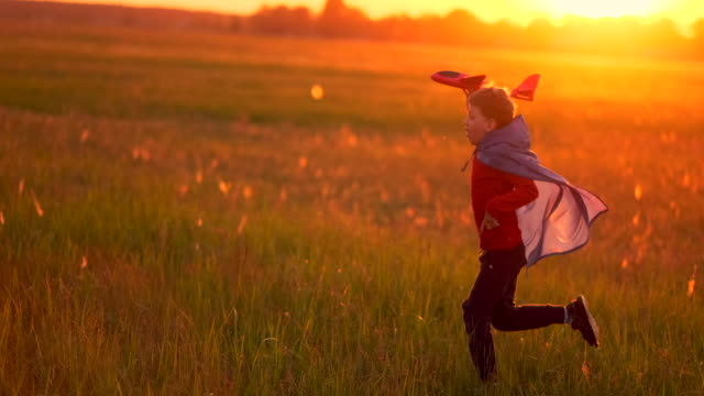A child at sunset fantasizes and imagines himself a pilot at sunset A happy boy with a raincoat imagines himself an airplane pilot and runs with a toy across the field thinking that he is an airplane pilot at sunset. work helmet stock videos & royalty-free footage