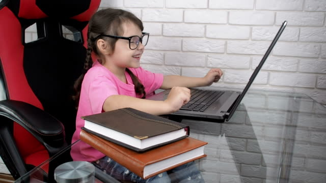 Child at the laptop. Typing on keyboard. Child at the laptop. Typing on keyboard. А little girl with glasses typing on the keyboard and looking at the screen every two seconds pigtails stock videos & royalty-free footage