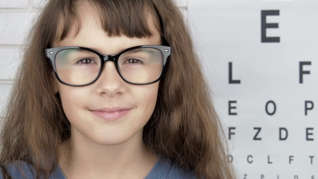 Child at the ophthalmologist. Child at the ophthalmologist. Little girl puts on glasses. eye chart stock videos & royalty-free footage
