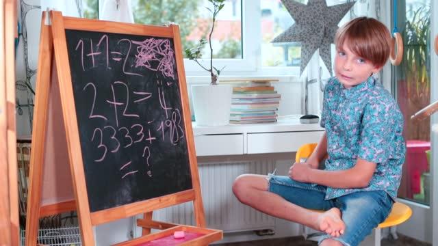 un bambino blogger insegna una lezione di matematica online per i suoi compagni di classe. - didattica a distanza video stock e b–roll