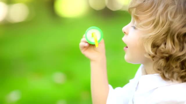 Child blowing soap bubbles. Slow motion video