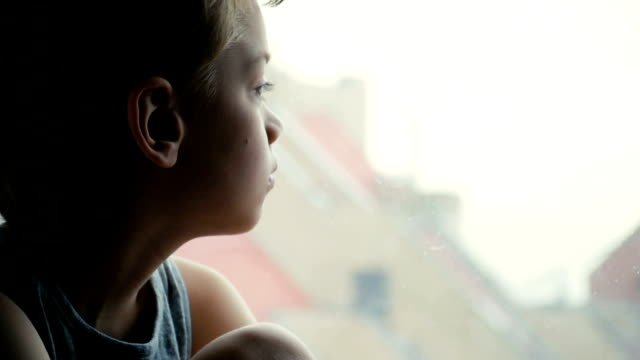 Child boring Boy bored sitting at home by the window, close up boys stock videos & royalty-free footage