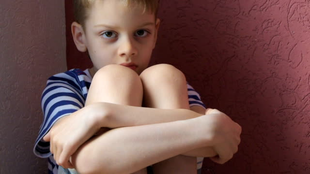 Child boring Bored boy sitting at home in corner of room depression land feature stock videos & royalty-free footage