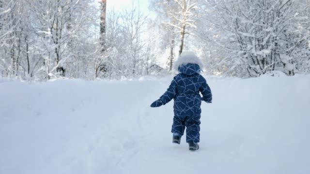 garçon d'enfant dans la salopette d'hiver fonctionnant sur un chemin couvert de neige - Vidéo