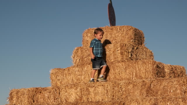 Child boy playing at a pumpkin patch haystack pyramid