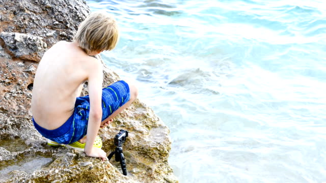 Child boy shooting movie with action outdoor waterproof camera in the sea video