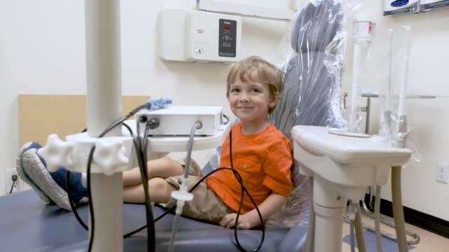 vídeos y material grabado en eventos de stock de niño sentado en la oficina del dentista - ortodoncista