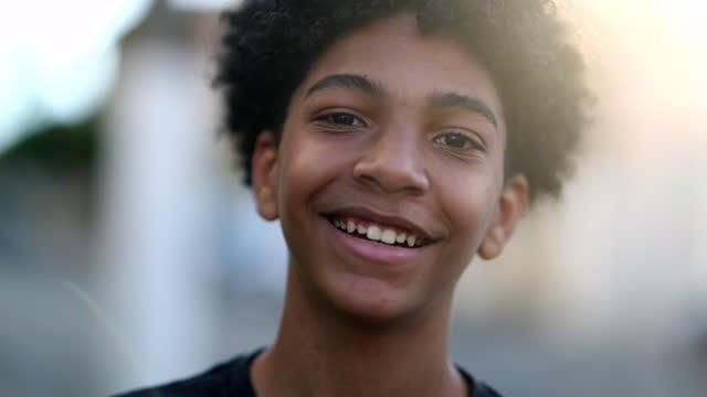 vídeos de stock e filmes b-roll de child boy smiling to camera portrait, mixed race kid, ethnically diverse boy smile in sunlight outdoors - castanho