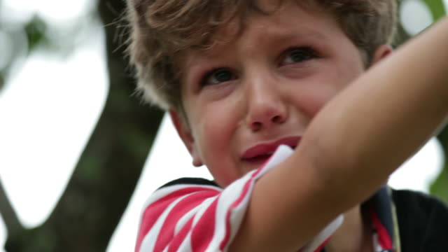child crying in tears. real life authentic candid sobbing of a tearful child on top of a tree. inconsolable crying young boy is sobbing in 4k - divorzio video stock e b–roll