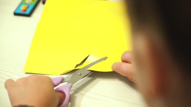 bambino taglia la carta con le forbici. - forbici video stock e b–roll