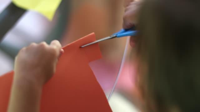 vídeos de stock e filmes b-roll de child cutting paper with scissors. kid crafting at home - cortar atividade