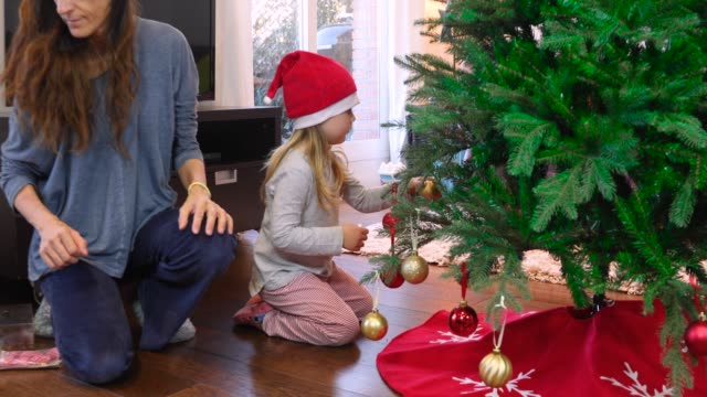 child decorating christmas tree with mother video