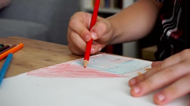 vidéos et rushes de un enfant dessine une maison avec des crayons de couleur - hlm