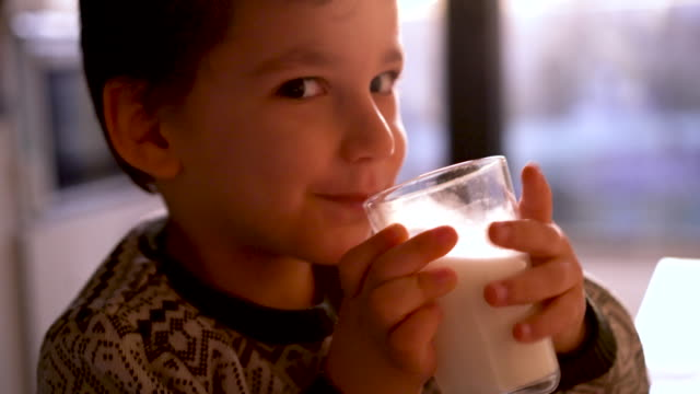 Child Drining Milk 4 years old boy drinking a glass of milk. 4k Video footage of an adorable little boy enjoying a glass of milk at home. turkey middle east stock videos & royalty-free footage
