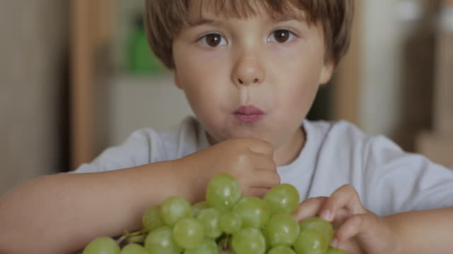 Child Eat Sweet Grape. Little Boy Vegetarian is Eating White Grapes From Plate Sitting Home at Table in Kitchen. Healthy Organic Vegetarian Food. Fruit harvest.