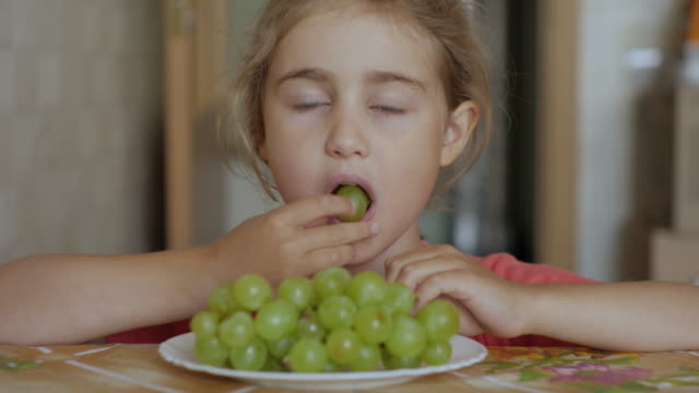 Child Eat Sweet Grape. Little Girl Vegetarian is Eating White Grapes From Plate Sitting Home at Table in Kitchen. Healthy Organic Vegetarian Food. Fruit harvest.