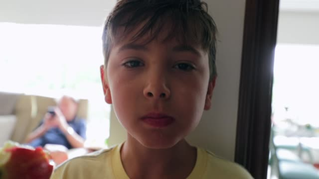 child eating apple and looking to camera. casual candid clip of handsome young boy eating fruit indoors - pesche bambino video stock e b–roll