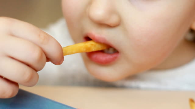 Child eating french fries closeup. Portrait of a baby who eats fast food Child eating french fries closeup. Portrait of a baby who eats fast food french fries stock videos & royalty-free footage