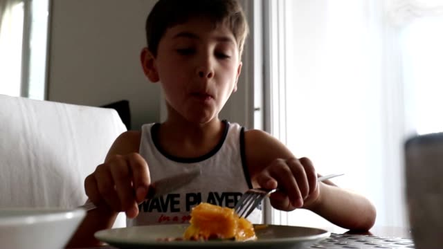 child eating fruit for breakfast. kid cutting peach with fork and eating. mom with toddler in the background - pesche bambino video stock e b–roll