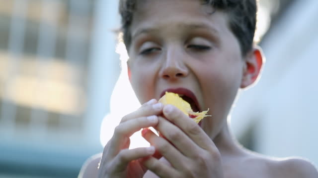 child eating fruit outside with lens-flare - pesche bambino video stock e b–roll