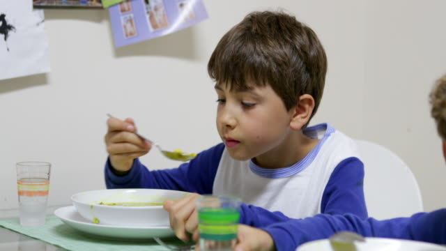child eating healthy soup. young boy sipping healthy vegetable soup in 4k. kid casually sipping soup with spoon in 4k - pesche bambino video stock e b–roll
