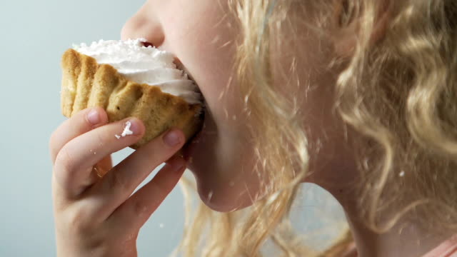 Child eating high-caloried cream cake with mess, dangerous sweet sugary junkfood video