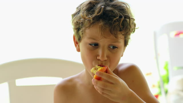 child eating peach fruit  portrait of young boy eating healthy food - pesche bambino video stock e b–roll