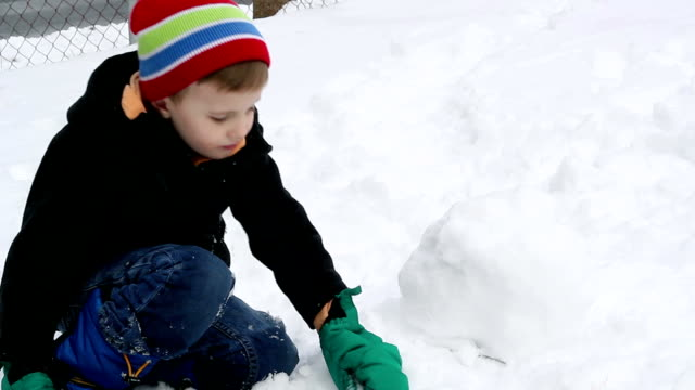 Child Eating Snow and Making a Snow Ball video
