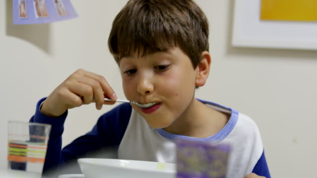child eating soup in 4k. candid casual natural moment of young boy sipping soup with spoon casually in 4k - pesche bambino video stock e b–roll