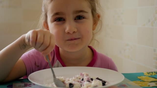 ein kind isst ein quarkdessert mit johannisbeerbeeren. ein kleines mädchen isst hüttenkäse. - quark stock-videos und b-roll-filmmaterial