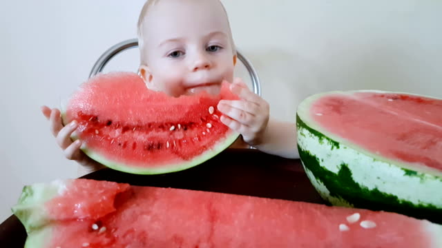 Child eats red slice of watermelon video