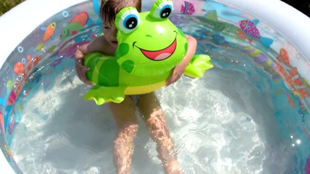 vídeos de stock e filmes b-roll de child enjoying bathing on hot summer day - brinquedos na piscina