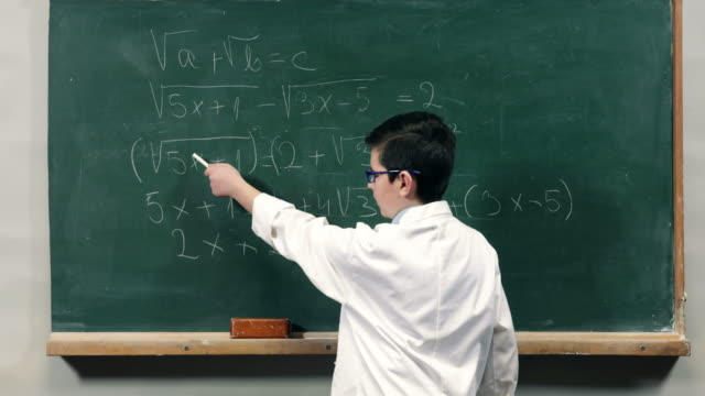 Child explaining a mathematical equation on blackboard Child wearing a lab coat, explaining a mathematical equation on blackboard at school mathematics stock videos & royalty-free footage